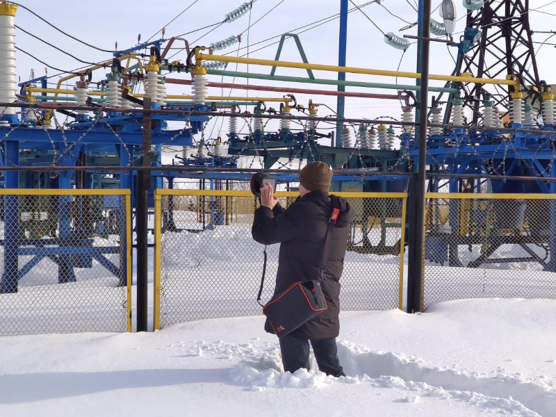 A man in snow uses an ultrasonic acoustic camera to detect partial discharges in power grid